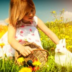 Girl petting Easter bunny on meadow with eggs