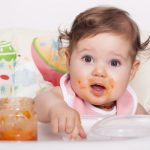 Adorable smudgy baby and favorite baby food in jar