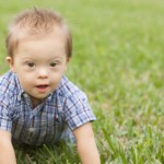 Down Syndrome child crawling in green grass