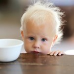 Sad Little One Year Old Baby Girl with Empty Cereal Bowl
