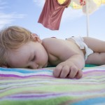 baby sleeping on beach towel