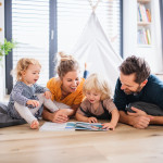 Young family with two small children indoors in bedroom reading a book.