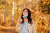 End of coronavirus epidemic concept. Millennial pregnant woman removing medical mask at autumn park